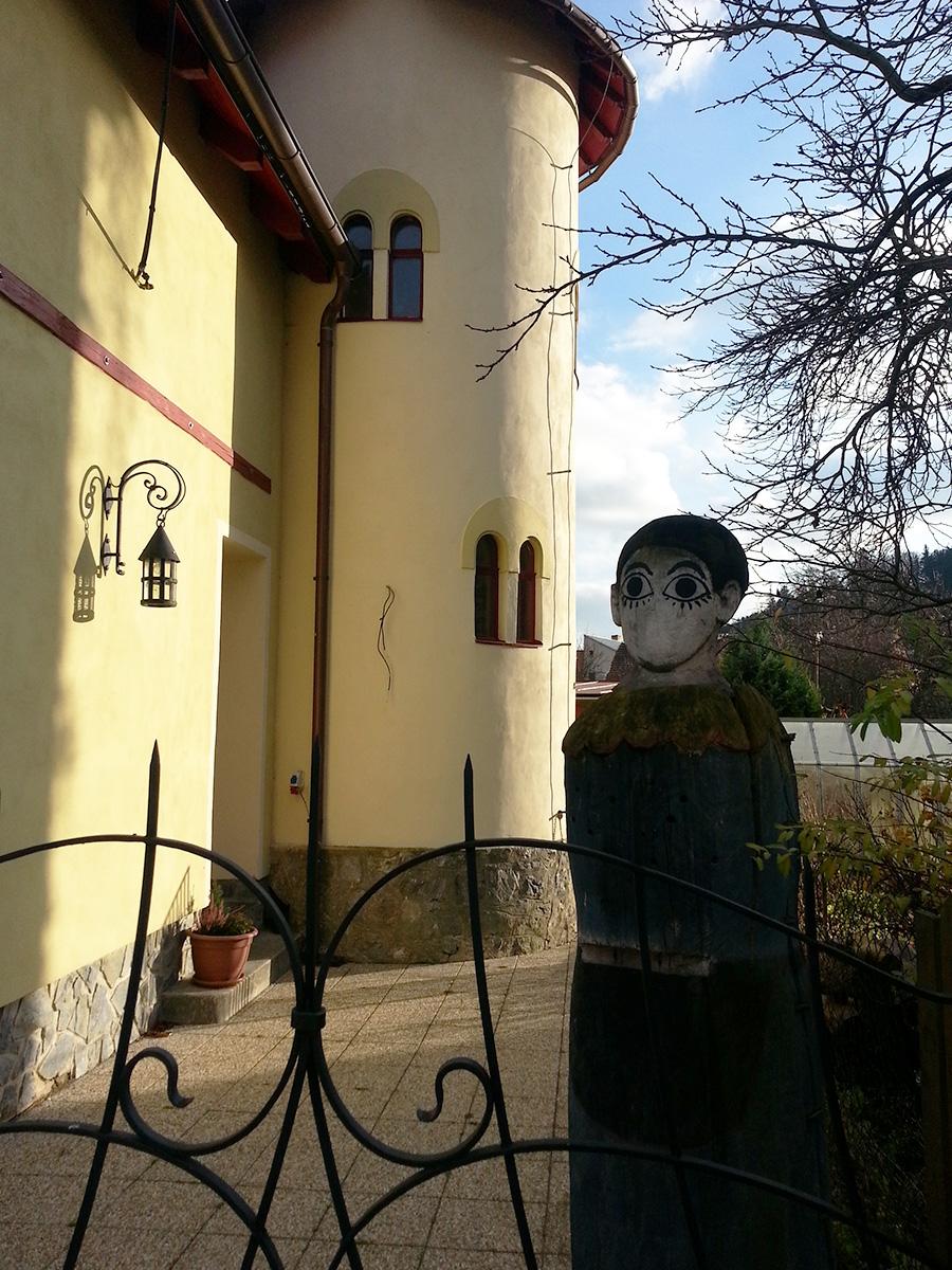 Dům s věžičkou a socha před domem